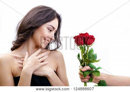 Beautiful girl receives three red roses. She is surprised, looking at the flowers and smiling. Men's hand holding three roses. Girl is white with bushy brown hair. Isolated on white background.