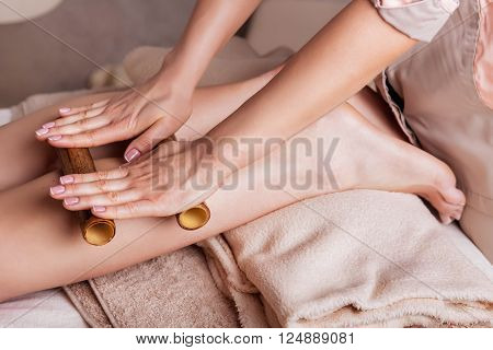 Massage of human foot in spa salon with bamboo sticks.