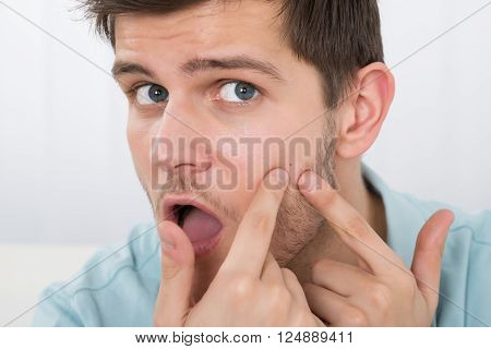 Photo Of Shocked Young Man Looking At Pimple