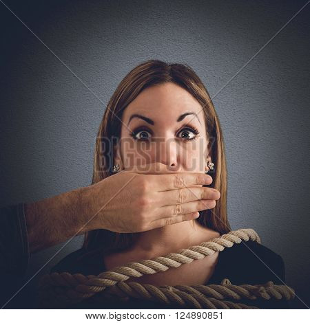 Man covering mouth to a woman tied