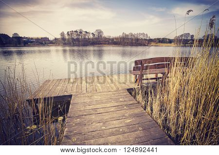 Vintage Toned Image Of A Bench On Wooden Pier.