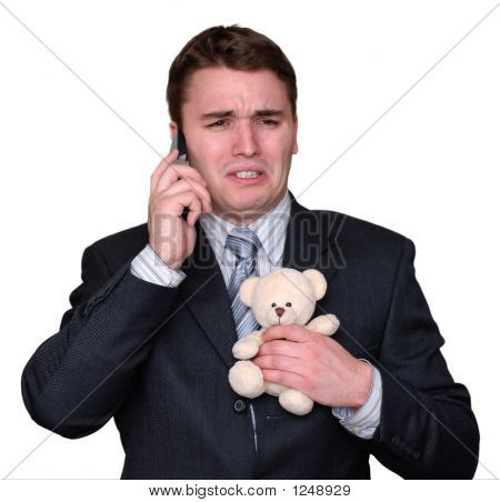 young Businessman Weinen auf Handy, Teddy Bear umklammert.