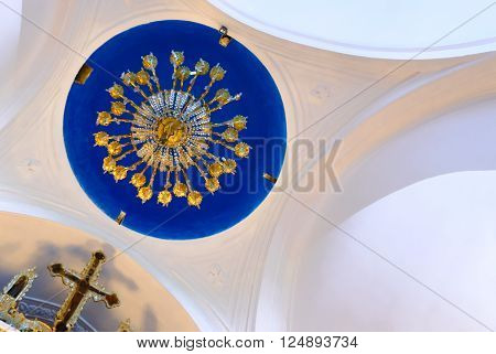 KYTHNOS, GREECE - AUGUST 14, 2014: Chandelier hanging from the cupola and the iconostasis cross, at the church of Panagia Stratolatissa