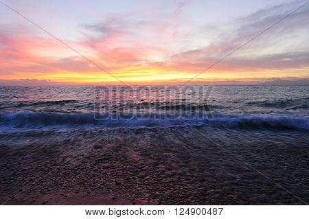 Ocean sunset is brightly lightred and golden seascape with a gentle wave rolling to the shore. ** Note: Shallow depth of field