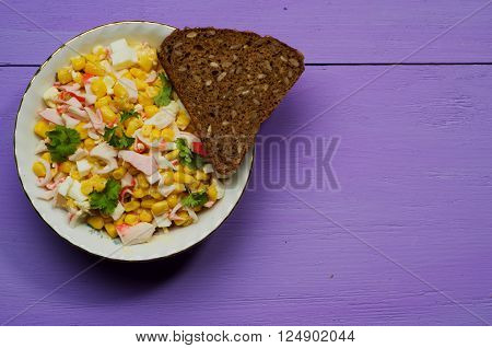 crab salad in a plate on a wooden table.Rustic style.  Free space for text.