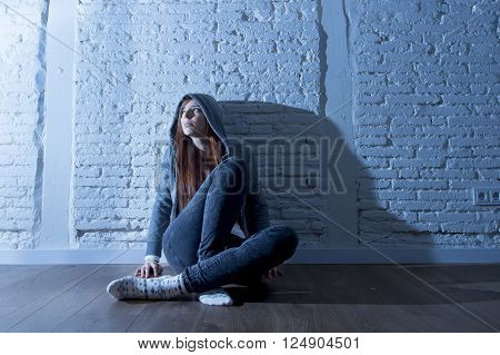 teenager girl or young woman with red hair wearing hood on feeling sad and depressed sitting on home floor in youth depression concept