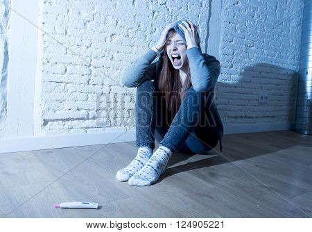 young red hair teenager girl or young woman screaming in shock and overwhelmed after positive pregnancy test sitting on floor devastated
