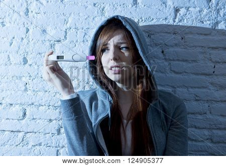 young red hair teenager girl or young woman worried in shock and overwhelmed after positive pregnancy test devastated and depressed in youth unwanted maternity concept