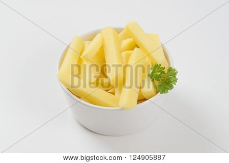bowl of raw french fries on white background