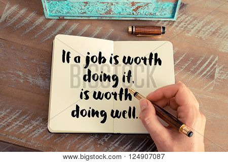 Retro effect and toned image of a woman hand writing on a notebook. Handwritten quote If a job is worth doing it is worth doing well as inspirational concept image