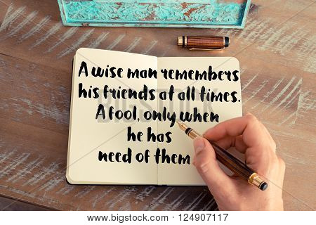 Retro effect and toned image of a woman hand writing on a notebook. Handwritten quote A wise man remembers his friends at all times; a fool, only when he has need of them as inspiration concept image