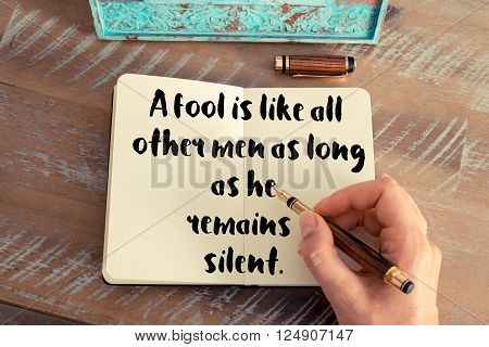 Retro effect and toned image of a woman hand writing on a notebook. Handwritten quote A fool is like all other men as long as he remains silent as inspirational concept image
