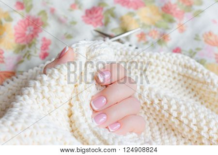 Little female hand with manicure holds connected to the spokes of a soft beige sweater yarn. Focus on the thumb.