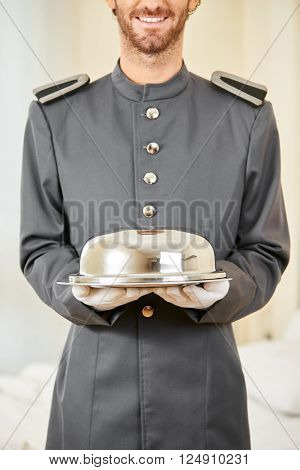 Friendly hotel page with food under cloche in a hotel room