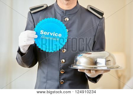 Hotel page holding service guarantee sign and food under cloche