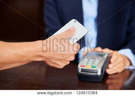Guest paying bill with his smartphone at the hotel reception