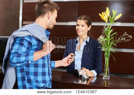 Male hotel guest paying with his credit card at reception