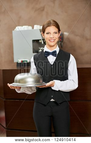 Female waiter in uniform with food under a cloche in a hotel restaurant