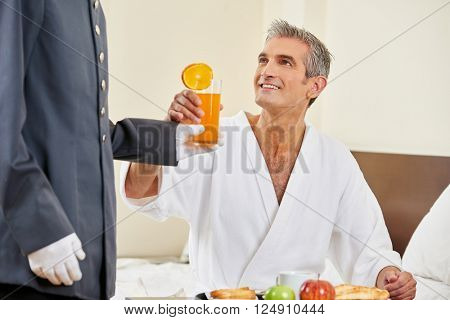 Room service bringing breakfast with orange juice to a hotel room guest