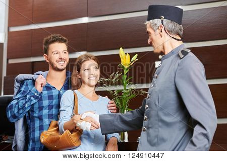 Concierge giving handshake to couple in hotel as welcome sign