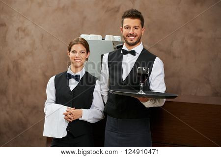 Waiter and sommelier serving red wine in a restaurant