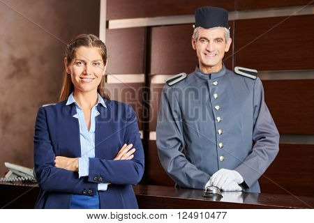 Happy concierge and smiling receptionist in a hotel as team in uniform