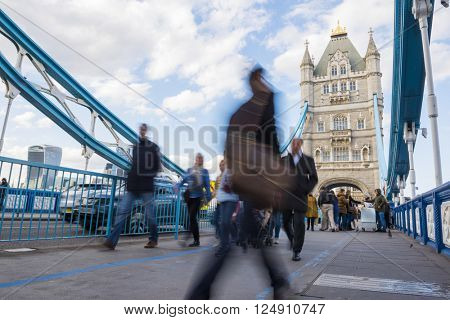 LONDON, UK APRIL 05 2016: Motion blurred commuters crossing Tower Bridge during rush hour. Tower Bridge links the South of River Thames to the City area.