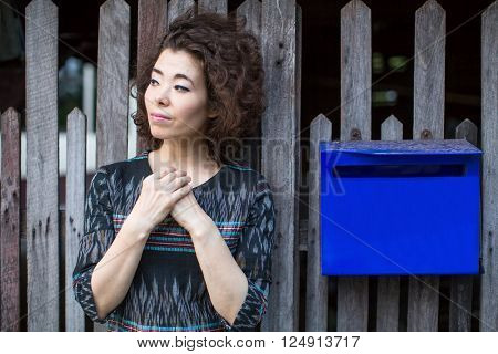 Asian woman stands near the fence with a blue mailbox.
