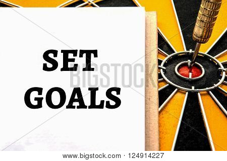 Words set goals with dart target arrow on the center of dartboard Smart goal target success business investment financial strategy concept abstract background