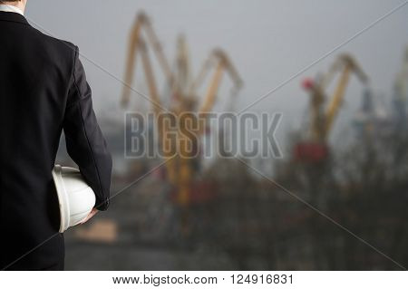 Close up of engineer hand holding white safety helmet for workers security standing in front of urban background.