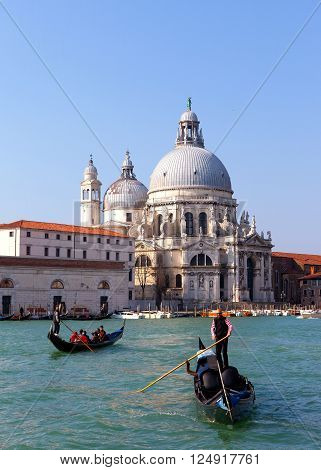 Venice, Italy - March 22, 2016: Gondoliers and Gondola at Venice grand canal with the Basilica di Santa Maria della Salute in the background