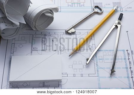 Architect worplace top view. Architectural project, blueprints, blueprint rolls and  divider compass, key, blank business card on plans. Construction background. Engineering tools. Copy space.