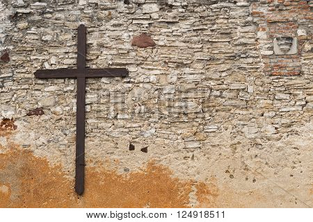 old wooden cross on stone wall background
