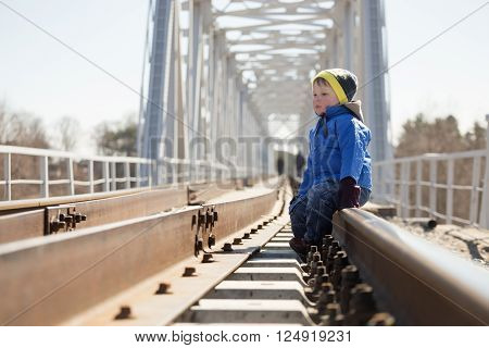 Portrait of a little boy sitting on the rails in the daytime. Belarus
