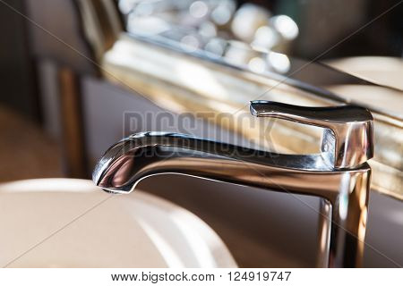 sanitary, plumbing and washing concept - close up of bath tap or faucet at bathroom