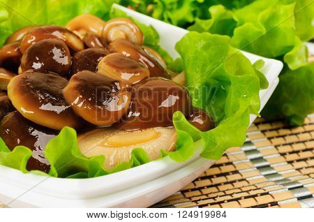 Marinated mushrooms with lettuce. The white plate on a bamboo napkin.