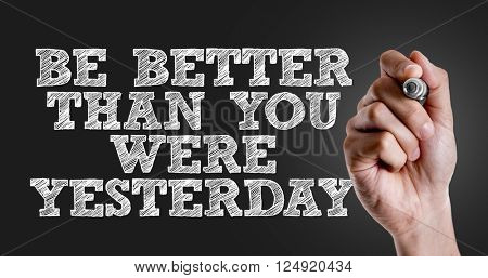 Hand writing the text: Be Better Than You Were Yesterday
