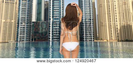 people, summer holidays, travel, tourism and vacation concept - woman in bikini swimsuit from back over dubai city and infinity edge pool background