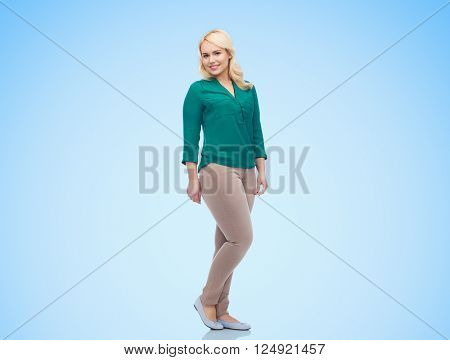 female, gender, portrait, plus size and people concept - smiling young woman in shirt and trousers over blue background