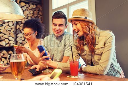 people, leisure, friendship, technology and communication concept - group of happy smiling friends with smartphones and drinks at bar or pub