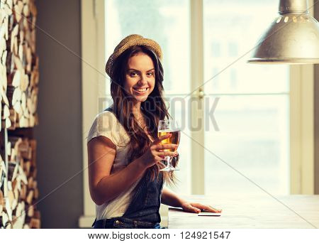 people, drinks, alcohol and leisure concept - happy young redhead woman drinking beer at bar or pub