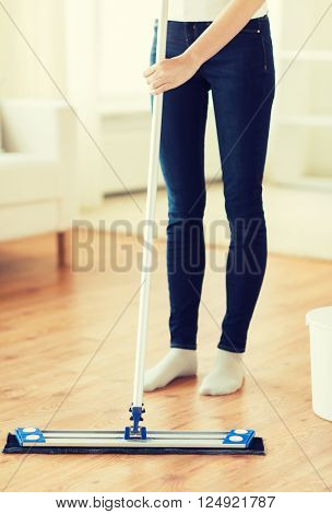 people, housework and housekeeping concept - close up of woman legs with mop cleaning floor at home