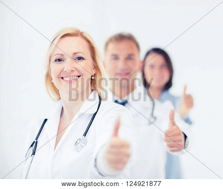 healthcare and medical concept - team of doctors showing thumbs up
