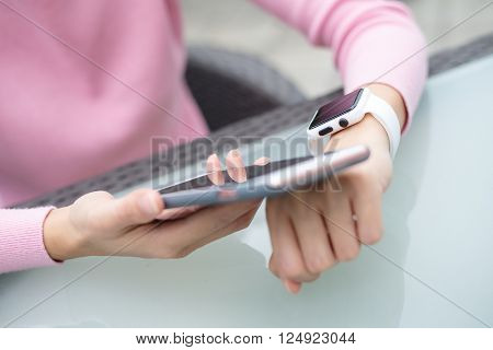 Woman using smart watch to connect with cellphone