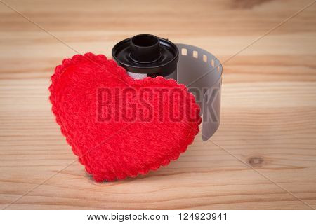 film cartridge with heart over wooden background