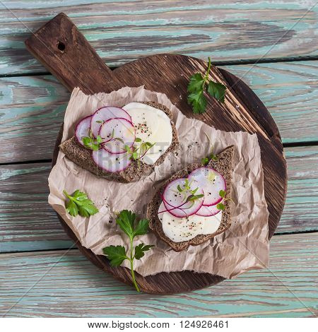 Open sandwich with cheese and radishes on rustic wooden cutting board on a light wooden background. Healthy breakfast or snack