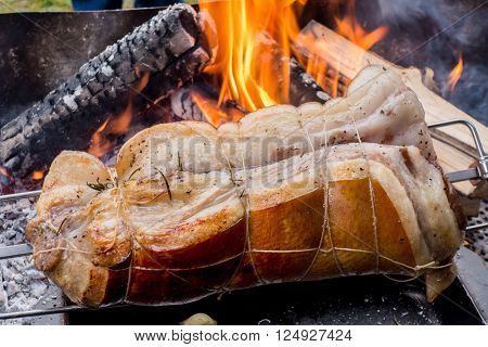 roast pig on a spit that runs on a barbecue