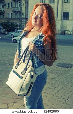 Redhair women with fashionable white handbag in the street in evening time.