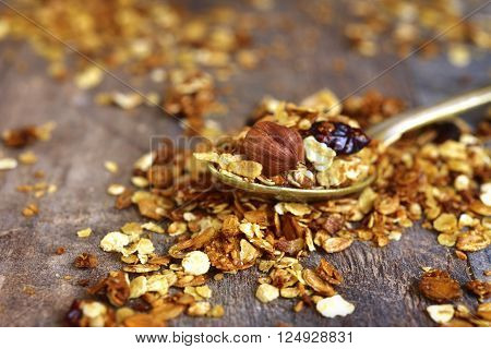 Granola On A Spoon On Rustic Background.