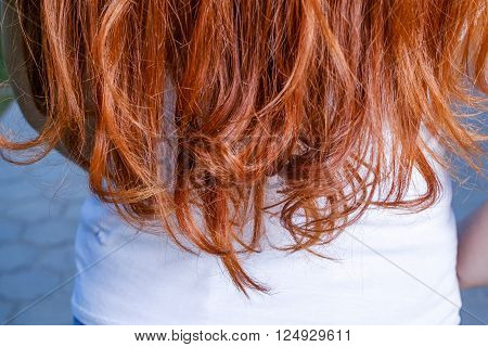Rear view of red haired woman and copyspace on shirt beneath.